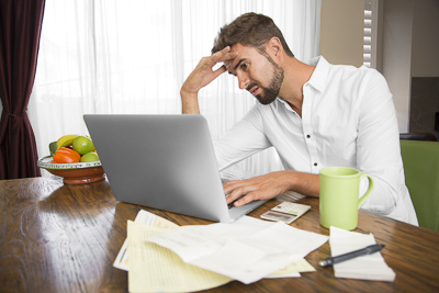Frustrated man trying to do his taxes at home