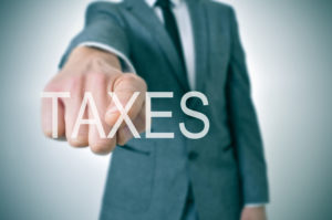 man wearing a suit pointing the finger to the word taxes written in the foreground